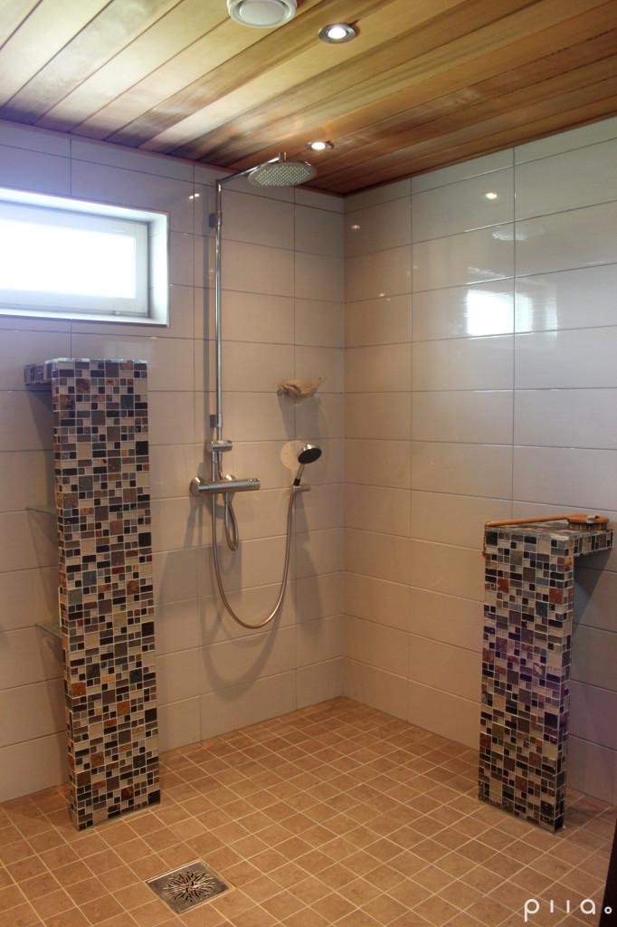 Kylpyhuoneen mosaiikkilaatoitetut säilytyshyllyt tekevät tilasta omaleimaisen.